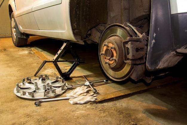 Mechaniker, der das autorad in der garage ändert mann, der reifen austauscht. reifenservice. reifenmontage.