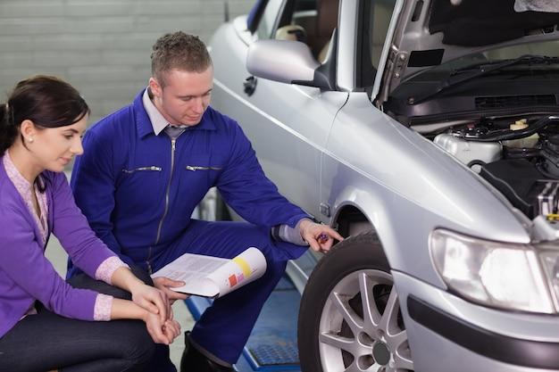 Mechaniker, der das autorad nahe bei einem kunden berührt