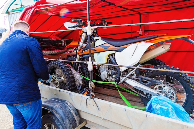 Mechaniker, der das motorradrad befestigt