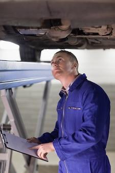 Mechaniker, der das unten von einem auto betrachtet