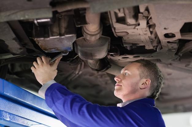 Mechaniker, der das unten von einem auto repariert