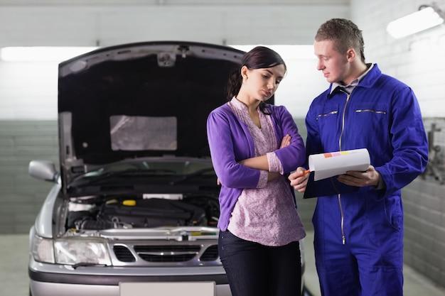 Mechaniker, der das zitat einem kunden zeigt