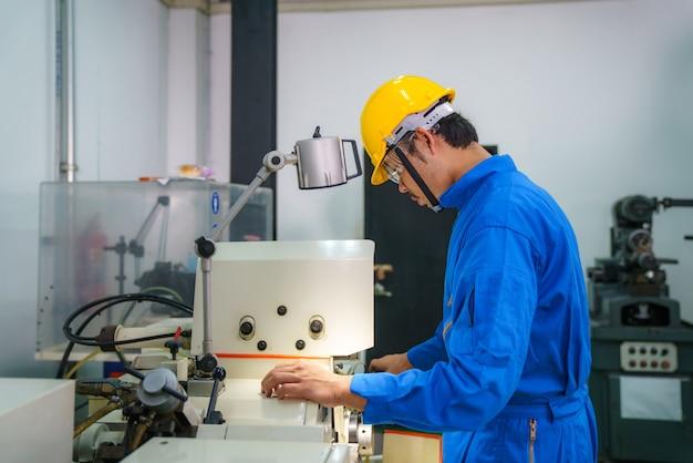 Mechaniker, der daten in der drehbank-cnc-maschine im werk in der werkzeugwerkstatt in der metallbearbeitungsindustrie eingibt.