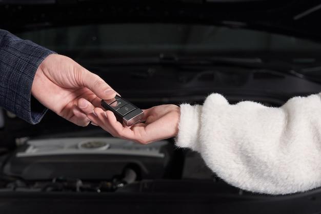Mechaniker, der dem kunden nach der wartung autoschlüssel gibt
