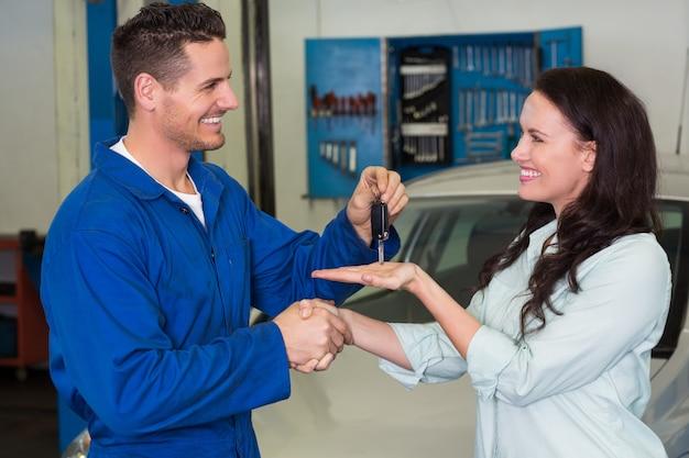 Mechaniker, der dem zufriedenen kunden schlüssel gibt