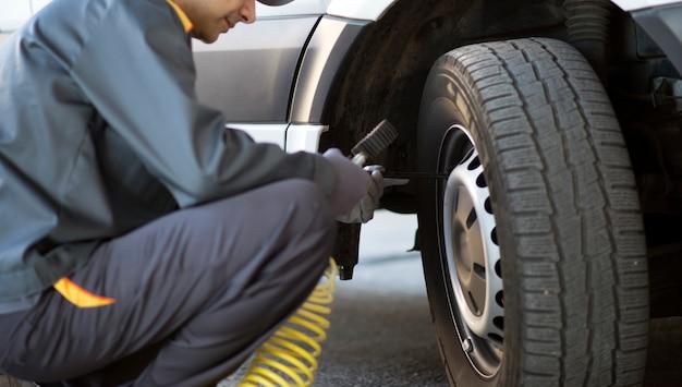 Mechaniker, der den druck eines van-reifens überprüft