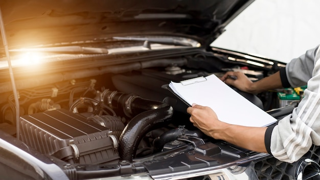 Mechaniker, der den motor eines wartungskonzeptfahrzeugs überprüft
