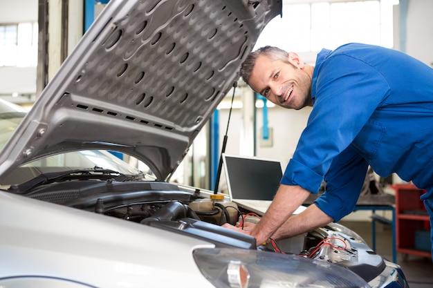 Mechaniker, der diagnosewerkzeug auf motor verwendet