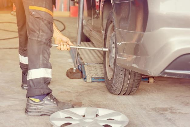Mechaniker, der die achsmessvorrichtung an einem autoreifen eines neuen reifenaustauschs befestigt