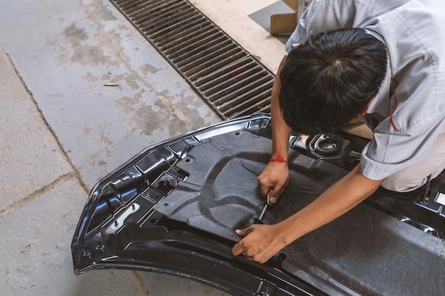Mechaniker, der die autotür repariert