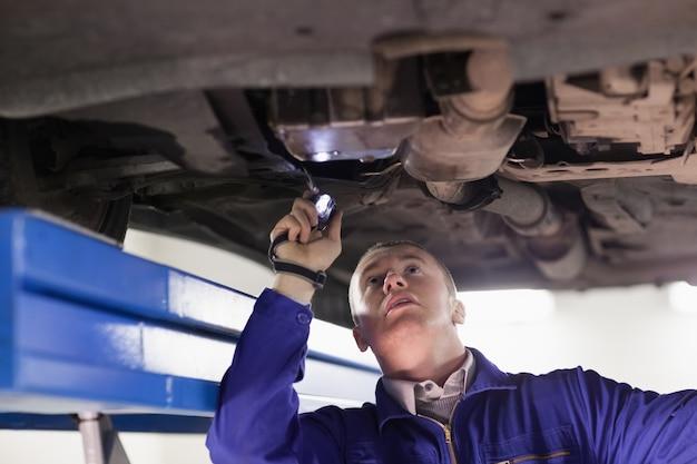Mechaniker, der ein auto beim halten einer taschenlampe betrachtet