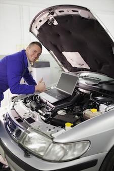 Mechaniker, der ein auto mit einem computer repariert