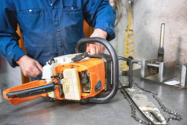 Mechaniker, der eine kettensäge repariert. mann, der eine kettensäge im werktisch repariert.