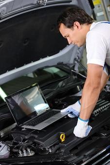 Mechaniker, der eine laptop-computer verwendet, um einen automotor zu überprüfen.