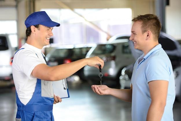 Mechaniker, der einem kunden in einer garage autoschlüssel gibt.