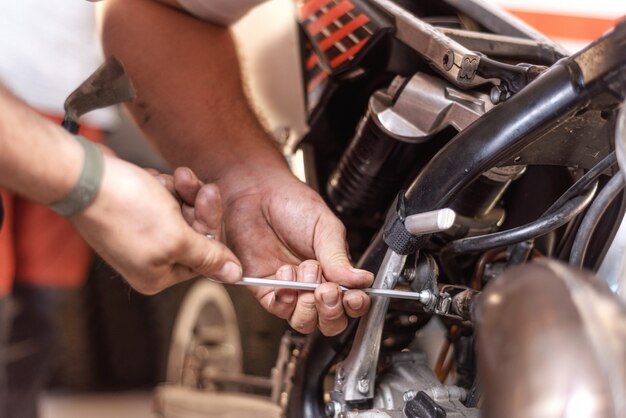Mechaniker, der einen motorradmotor in einer werkstatt repariert.