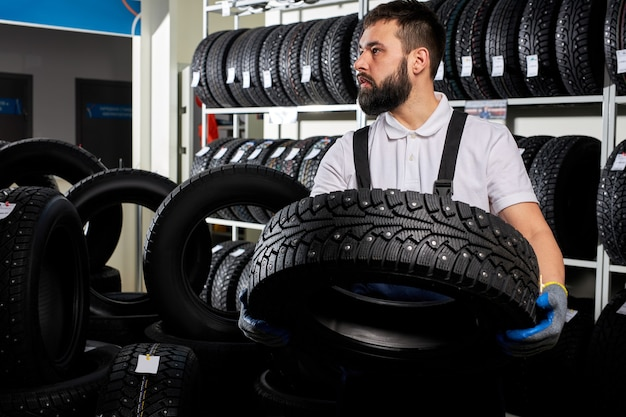 Mechaniker, der einen reifen hält und radreifen am autoreparaturdienst und im autohausladen zeigt, junger bärtiger mann in der uniform, die in der autowerkstatt arbeitet