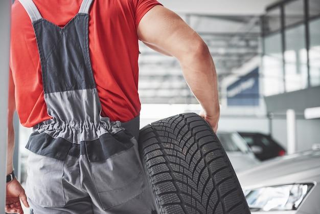Mechaniker, der einen reifenreifen in der reparaturwerkstatt hält. austausch von winter- und sommerreifen.