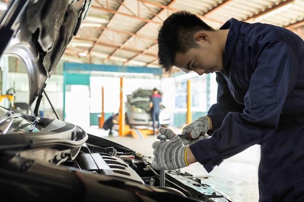 Mechaniker, der einen schlüssel und einen schraubenzieher verwendet