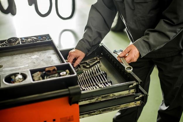 Mechaniker, der einrichtungen von der speziellen box für mechanische instrumente nimmt.