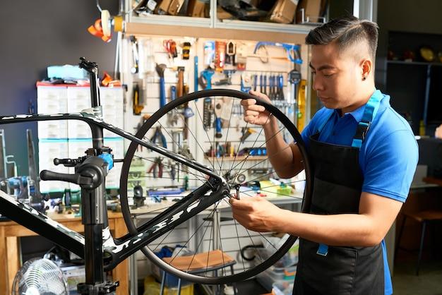 Mechaniker, der fahrradräder zusammenbaut