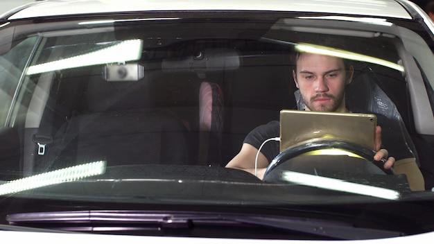 Mechaniker, der im auto sitzt und diagnose auf digitalem tablett tut.