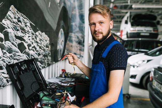 Mechaniker, der mit drähten an der werkstatt arbeitet