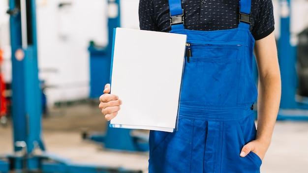 Mechaniker, der ordner mit sauberem papierblatt hält