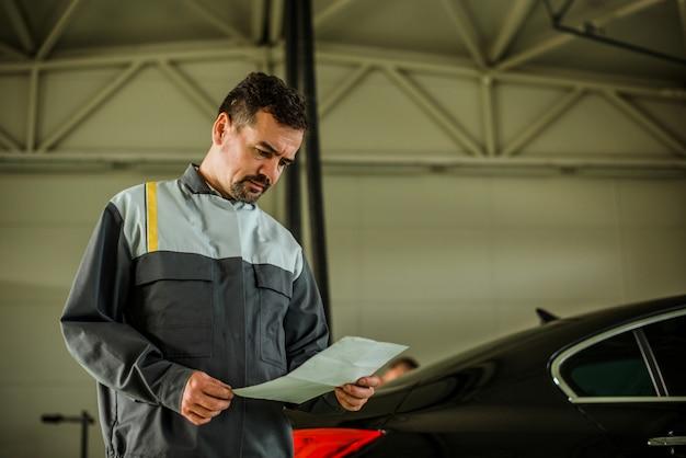 Mechaniker, der papier in der garage betrachtet.