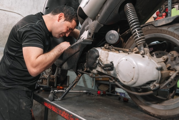 Mechaniker, der rollermotorrad in der reparaturgarage repariert.