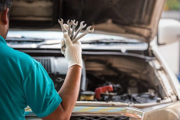Mechaniker, der schlüssel in der hand, automobilwartungsservice hält.