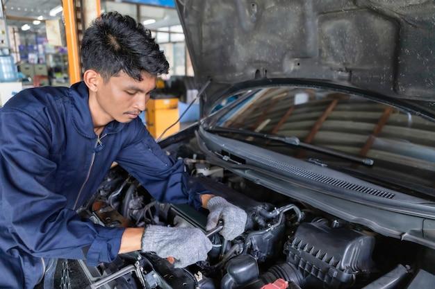Mechaniker, der schlüssel und einen schraubenzieher verwendet, um zu arbeiten