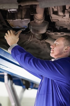 Mechaniker, der unten von einem auto mit einem schlüssel repariert