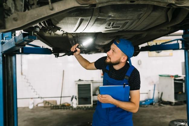 Mechaniker, der unterseite des autos überprüft
