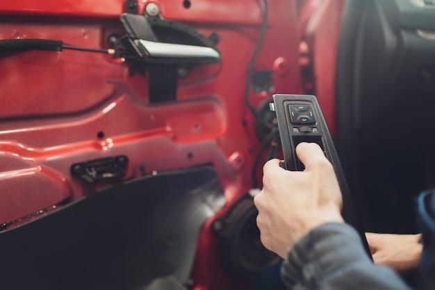 Mechaniker, der zentralverriegelungsmotor des autos installiert.