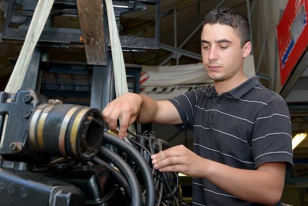Mechaniker des jungen mannes, der motorboote und anderes repariert