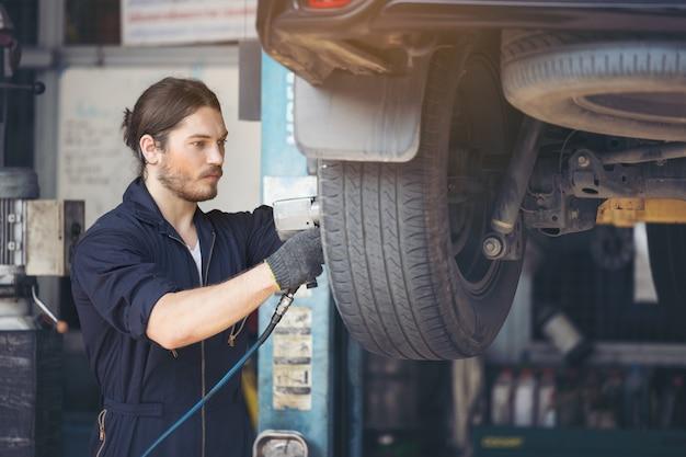 Mechaniker, die autoreifen in der garage reparieren