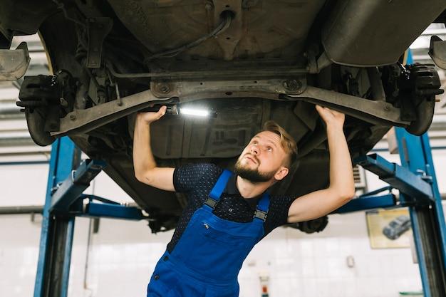 Mechaniker, die das fahrzeuggetriebe inspizieren