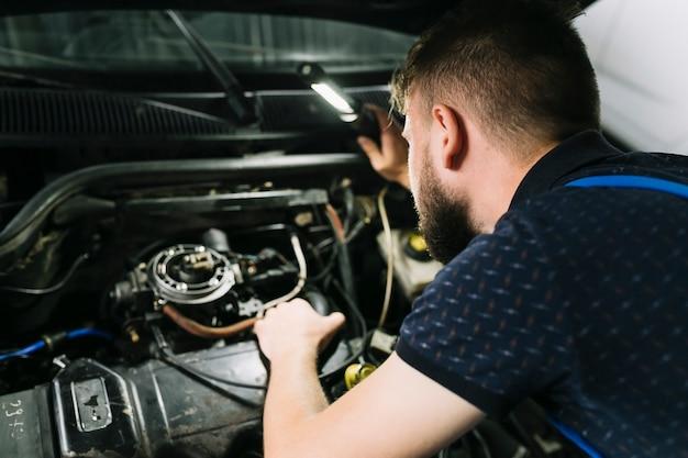 Mechaniker, die den fahrzeugmotor inspizieren