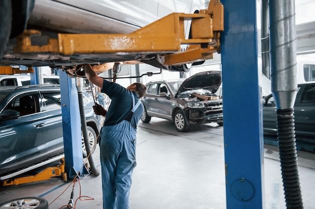 Mechaniker, die mit kaputtem auto im fahrzeugsalon arbeiten. viele transporte im raum.
