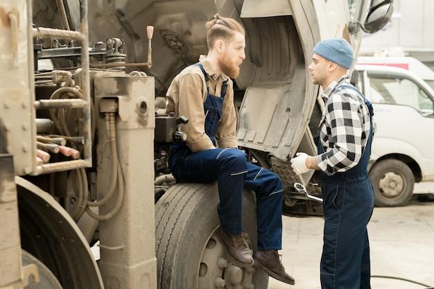 Mechaniker diskutieren reparatur von lkw