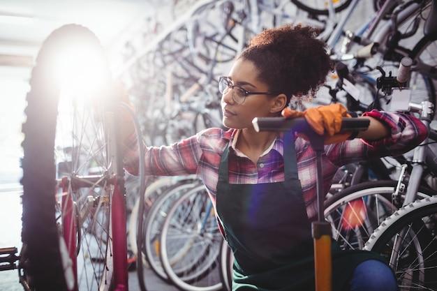 Mechaniker füllung luft in fahrradreifen mit luftpumpe