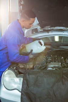 Mechaniker gießt öl schmiermittel in den automotor