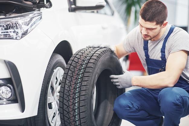 Mechaniker hält einen reifenreifen in der reparaturwerkstatt. austausch von winter- und sommerreifen