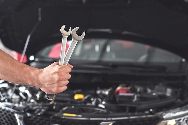 Mechaniker hält zwei schraubenschlüssel in der reparaturwerkstatt.