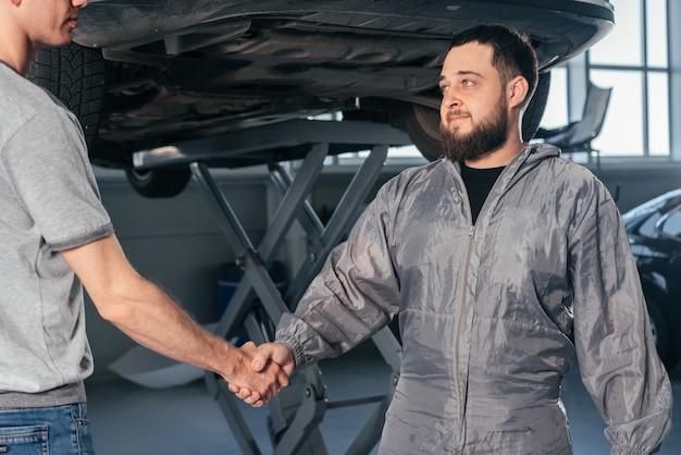 Mechaniker händeschütteln mit autobesitzer im werkstattwagen-autoservice-konzept