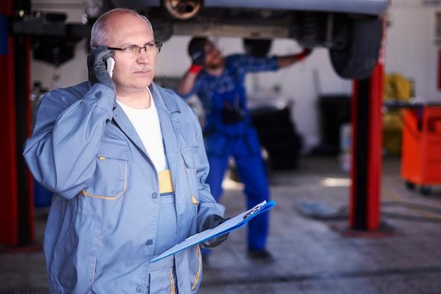 Mechaniker im gespräch mit einem kunden in der werkstatt