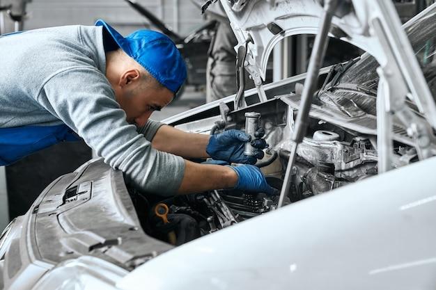 Mechaniker in blauen overalls prüft die gebrauchstauglichkeit des automotors