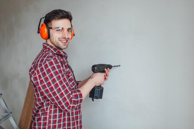 Mechaniker in brille und mit einem bohrer in der hand