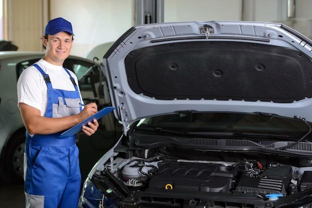 Mechaniker in der autowerkstatt, die nahe bei auto steht.